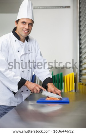 Smiling chef cutting raw salmon with knife on blue cutting board in professional kitchen - stock photo