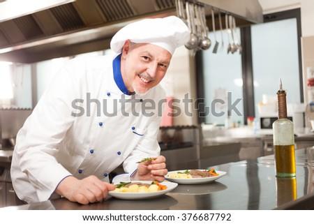 Smiling chef garnishing a dish - stock photo
