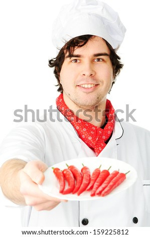 Smiling chef in uniform holding a plate of hot chili peppers - stock photo