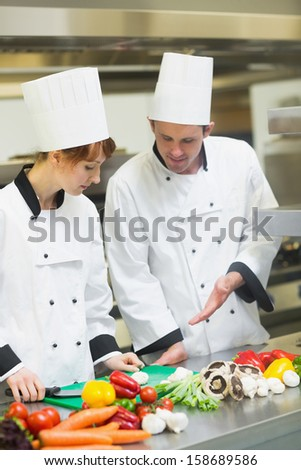 Smiling chef looking at his colleagues sliced mushrooms in busy kitchen - stock photo