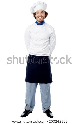 Smiling chef posing casually with his hands behind - stock photo