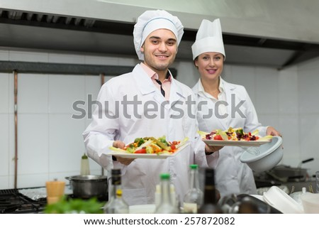Smiling chef with assistant cooking at kitchen in the restaurant. Focus on man - stock photo