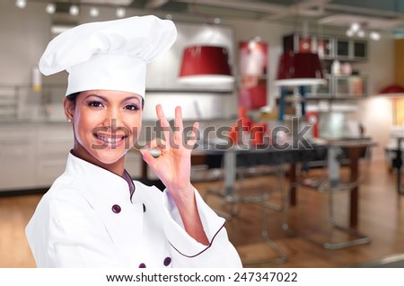 Smiling chef woman in the kitchen - stock photo