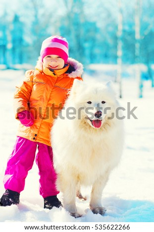 smiling child and white Samoyed dog playing on snow winter