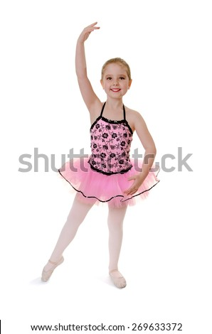 Smiling Child Ballerina Performs Tendu in Recital Tutu Costume - stock photo