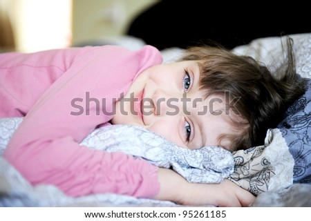 Smiling child girl relaxing in bed in early morning - stock photo