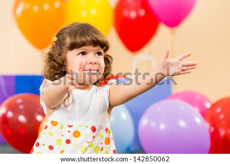 smiling child girl with balloons on birthday party - stock photo