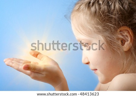 smiling child holding a sun at her hands on a blue sky background - stock photo