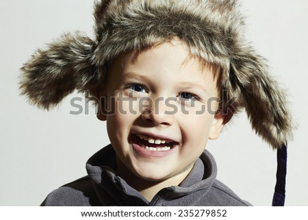 smiling child in fur Hat.Kids casual winter style.fashion little funny boy.children emotion.hat ear flaps - stock photo