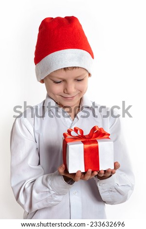 Smiling child in Santa red hat holding Christmas gift in hands. Christmas concept. - stock photo