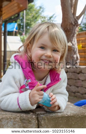 smiling child in the home garden playing with sand