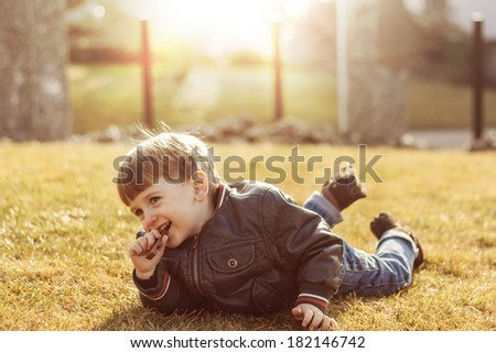 Smiling child lieing on the grass - stock photo
