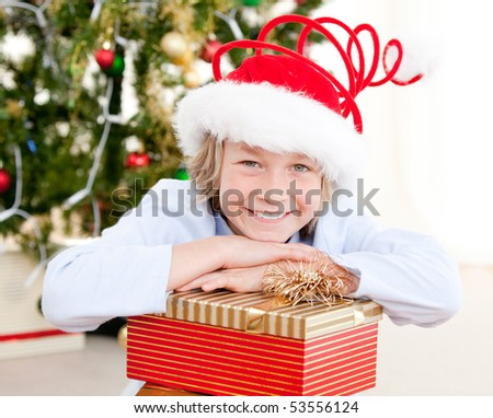 Smiling child opening his present at christmas time - stock photo