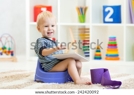 smiling child sitting on chamber pot indoors - stock photo