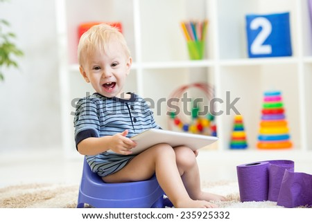 smiling child sitting on chamber pot playing tablet pc - stock photo