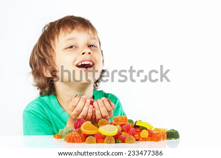 Smiling child with jelly candies on a white background - stock photo