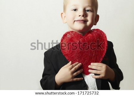 Smiling Child with Red Heart. Four Years Old Boy with Heart Symbol. Lovely Kid in Black Suit Valentine's Day - stock photo