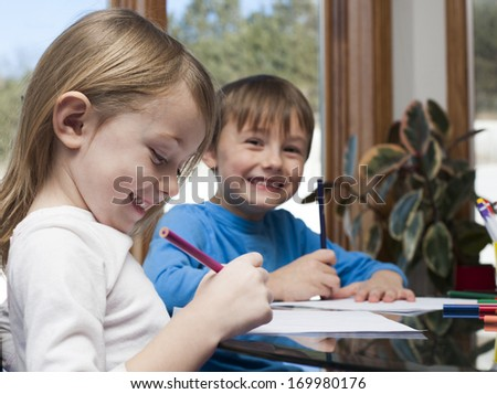 Smiling children drawing at the table