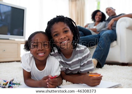 Smiling children drawing lying on the floor in the living room - stock photo