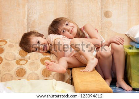Smiling children in a house situation (2 years and 5 years) - stock photo