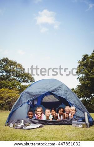 Smiling children lying in the tent together in the park on a sunny day