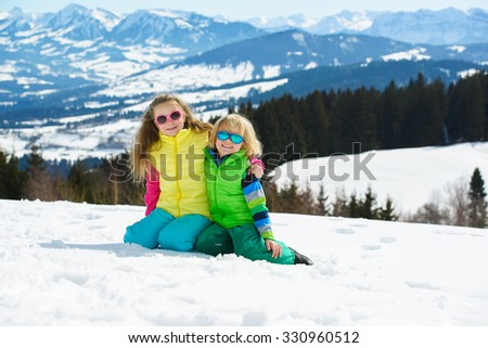 Smiling children playing with snow  in winter mountains on a sunny day - stock photo