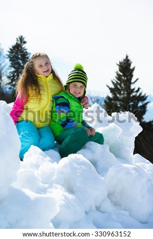 Smiling children playing with snow  on a sunny day  - stock photo