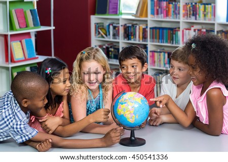 Smiling children with globe on table in library