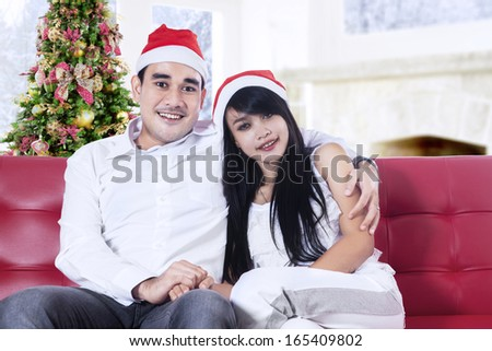 Smiling christmas couple wearing santa hats sitting on red sofa at home