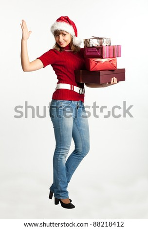 Smiling christmas girl holding gifts wearing Santa hat. Isolated on white background.