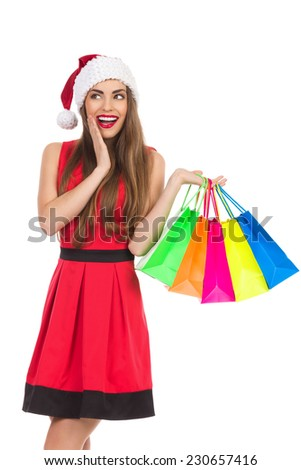 Smiling christmas girl with colorful shopping bags holding hand on chin and looking away. Three quarter length studio shot isolated on white. - stock photo