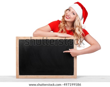 Smiling Christmas woman showing index finger with copy space for product or text a blank billboard, white background