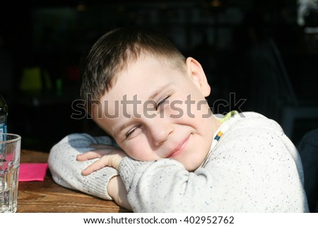 Smiling clever little boy sits at the desk - stock photo