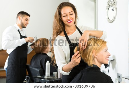 Smiling client sitting in a hair salon while hairdresser is combing her hair. Focus on client - stock photo