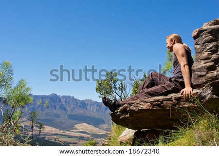 Smiling climber sits on top of mountain. Shot in Helderberg Mountains Nature Reserve, near Somerset West/Cape Town, Western Cape, South Africa.