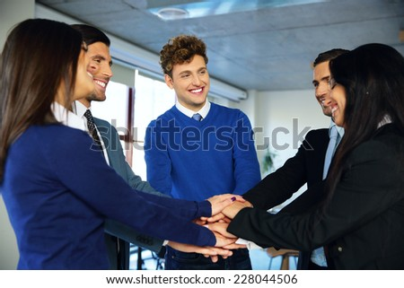 Smiling co-workers making pile of hands and looking at each other - stock photo
