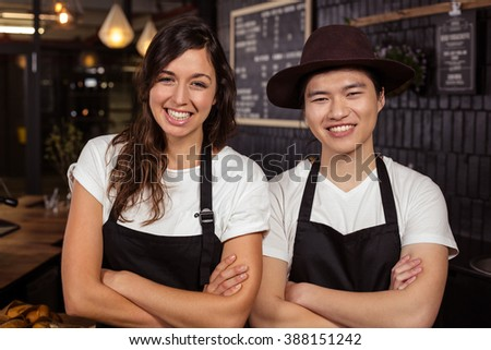Smiling co-workers posing with crossed arms at the coffee shop - stock photo