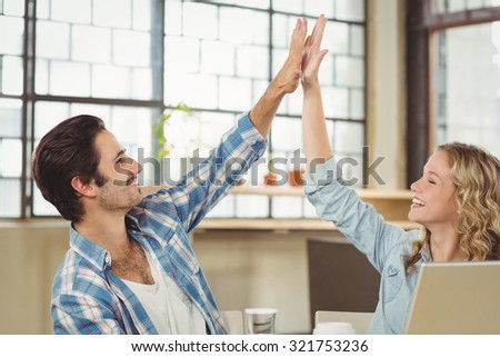 Smiling colleagues doing high five while working at office - stock photo