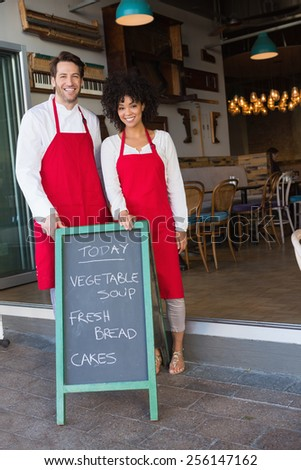 Smiling colleagues posing behind a chalkboard at the bakery - stock photo