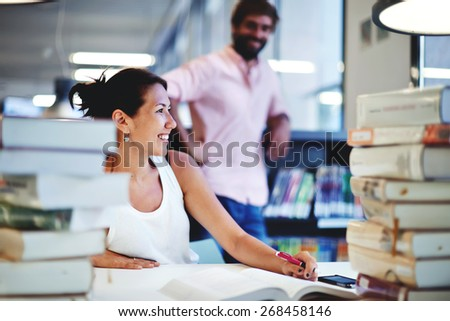Smiling college student sitting at the desk with huge pile of study books in university library, young asian female having fun with her male classmate in study hall of modern high business school - stock photo