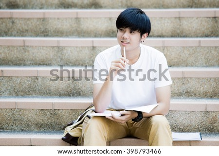 Smiling college student sitting on staircase - stock photo