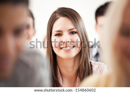 Smiling college student sitting surrounded by her friends. - stock photo