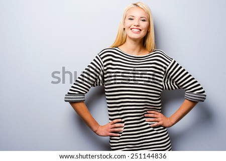 Smiling confidence. Beautiful young blond hair women holding hands on hip and looking at camera with smile while standing against grey background   - stock photo