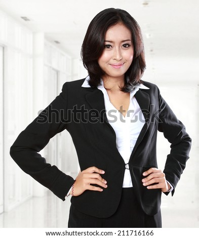 Smiling confidence young business woman in the office - stock photo