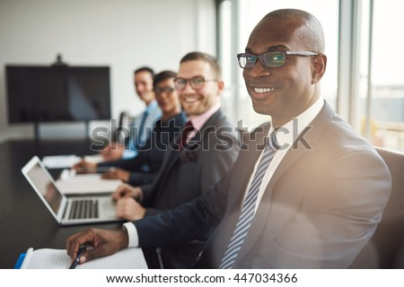 Smiling confident African businessman in a meeting with a group of multiracial co-workers seated at a conference table in the office - stock photo
