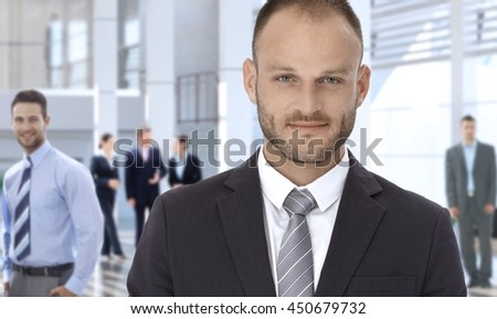 Smiling confident bristly caucasian businessman at business office center lobby, looking at camera. - stock photo