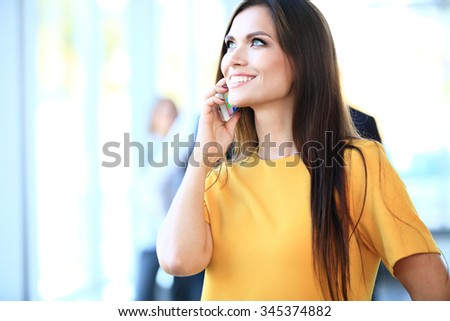 Smiling confident business woman having a phone call with her mobile phone, office interior on background - stock photo
