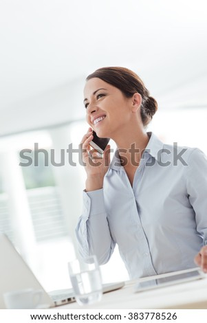Smiling confident business woman having a phone call with her mobile phone, office interior on background