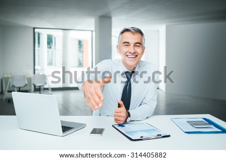 Smiling confident businessman giving an handshake, agreement and recruitment concept - stock photo