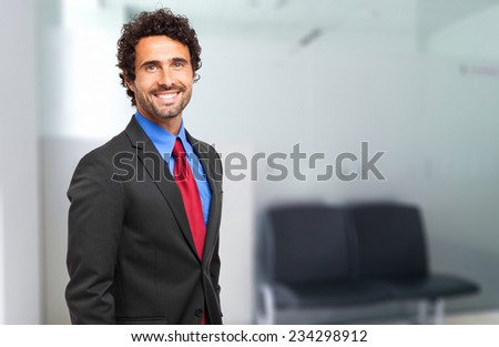 Smiling confident businessman in the office - stock photo